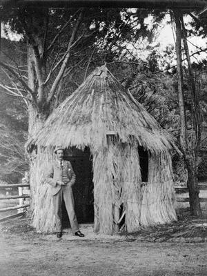 Hugh Douglas by flax hut at Waiwera