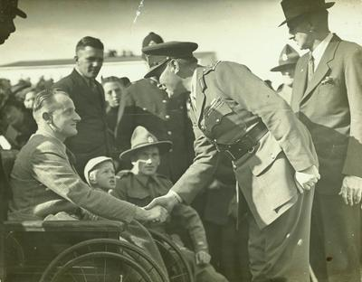 Lord Freyberg shaking hands with a man in a wheelchair