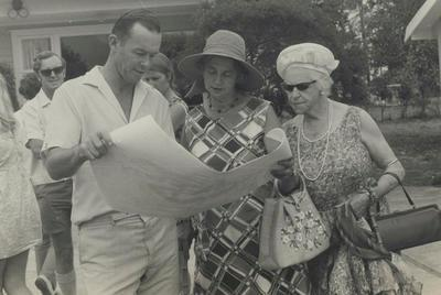 Murray Powell and two women viewing plan