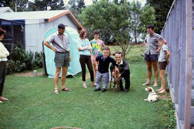 "Murray Powell looks on - visitors ""petting"" pet deer"