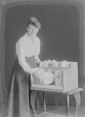Woman putting dish in cupboard