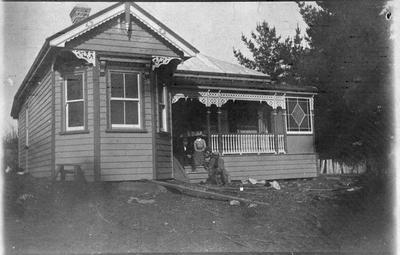 House and members of Wallis family sitting on the front steps