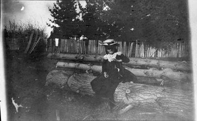 Girl and cat sitting on tree log