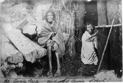 Two old Maori women and hut