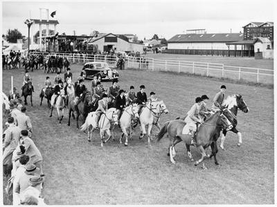 Pony club riders at Claudelands showgrounds followed by an Austin Sheerline car