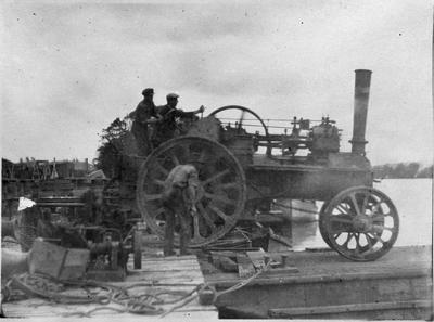 Driving tractor onto barge at Mercer workshop