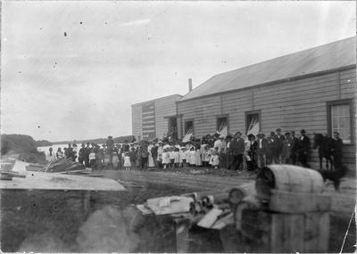 Large group of people (unidentified) with big building in background
