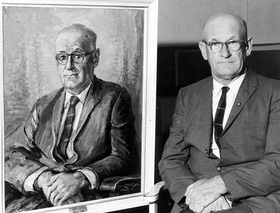 Mr Campbell seated beside portrait of himself painted by Ida Carey