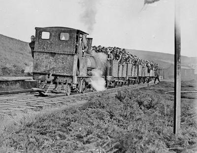 Locomotive pushing trucks with people (miners?)