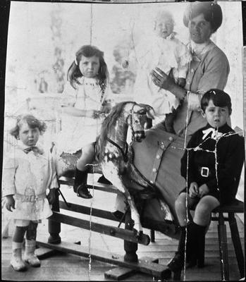 Mrs Florence Innes and four children, girl on rocking horse