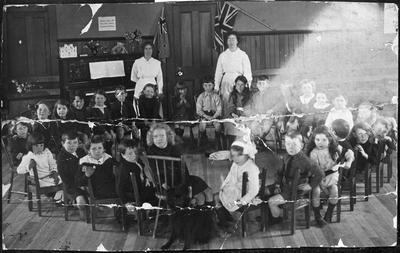 Children and two female teachers in classroom photo includes S Innes (Sydney Charles?)