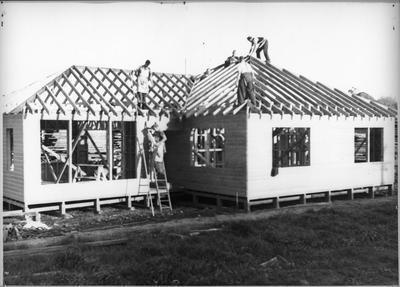 Ellis & Burnand constructing house in yard (x2)