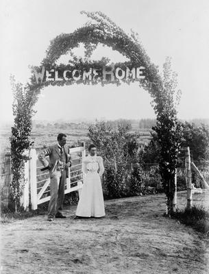 """""""welcome Home"""" Dr & Mrs H. Douglas under sign on archway"""