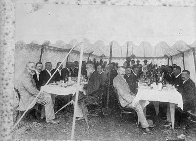 Group of people seated at tables in a tent