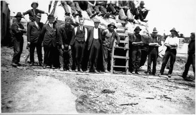 Men leaning against kauri log