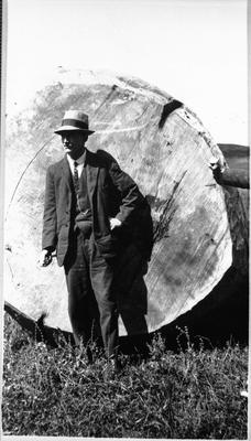 Man standing beside log
